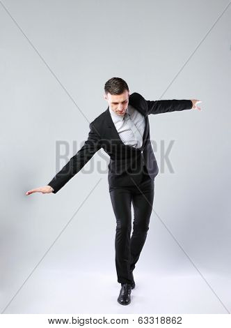 Businessman walking on invisible rope over gray background