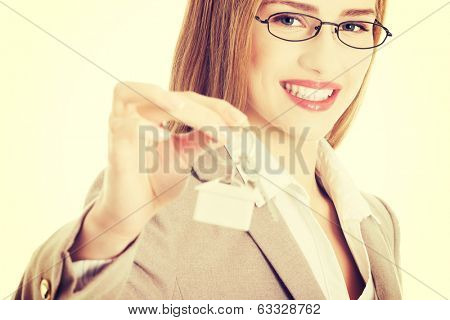 Caucasian business woman holds silver home keys.