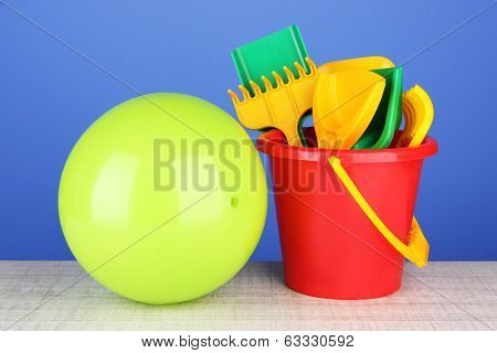 Bright ball and sandbox toys on table on blue background