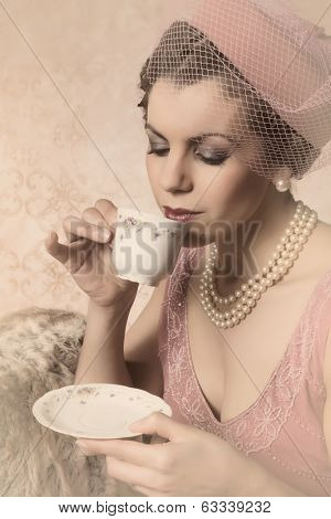 Attractive vintage 1920s lady with flapper dress and matching hat drinking tea