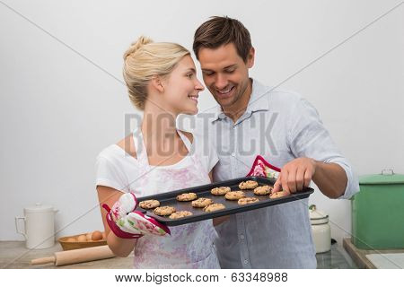 Happy young couple preparing cookies together in the kitchen at home