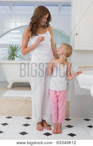 Little girl brushing teeth as she looks at her mother in the bathroom