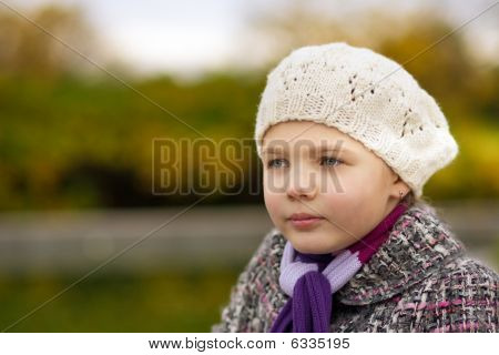 dreaming young girl in white beret near river bank