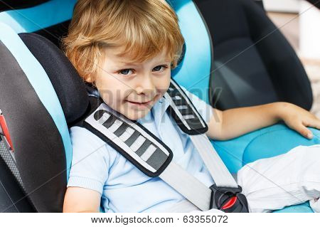 Little Boy Of 3 Years Sitting In Safety Car Seat.