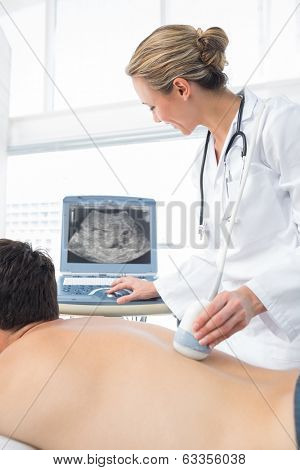 Female doctor using sonogram on back of male patient in examination room