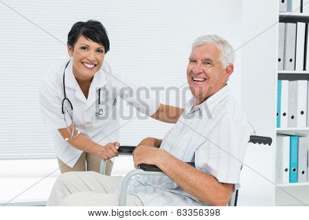 Side view portrait of a female doctor with senior patient in wheelchair at the hospital