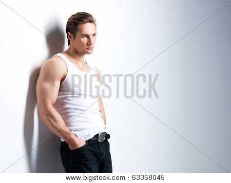 Fashion portrait of handsome young man in white shirt looking sideways poses over wall with contrast shadows.