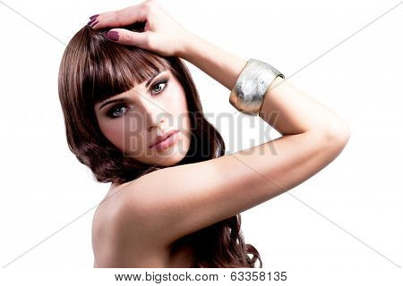 Portrait of young sexy woman with long brown hairs. Pretty girl model with stylish bijouterie of silver color.
