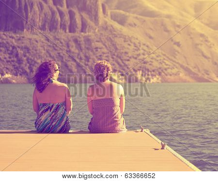 two women sitting on a dock done with a retro vintage instagram filter