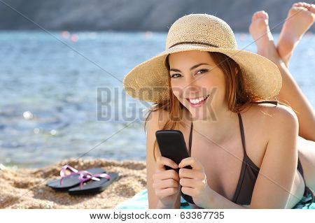 Woman Texting In A Smart Phone On Holidays On The Beach