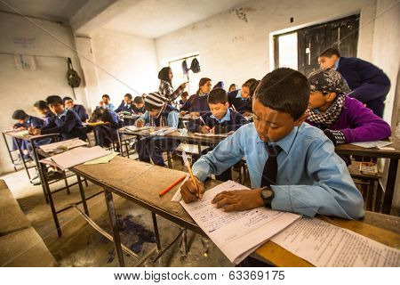 KATHMANDU, NEPAL - DEC 19, 2013: Unknown children in the lesson at public school. Adult literacy (age 15+) 60.3% (female: 46.3%, male: 73%) in a 2010 population census.