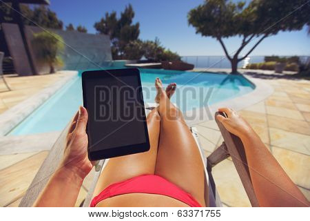 Woman On A Lounge Chair Using Tablet Pc Near The Pool