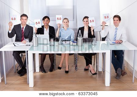 Businesspeople In Conference Holding Paper
