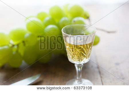 Glass of wine and white grapes on a old wooden table .