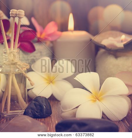 Wellness and spa concept with candles, frangipani flower, sandalwood and rattan sticks on massage table in vintage retro style.