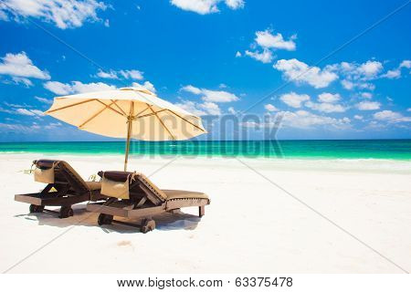 two beach chairs and umbrella on sand beach. Holidays