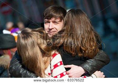 Young man embracing two girls on the street. All you need is love concept.