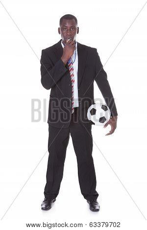 Businessman Blowing Whistle Holding Football