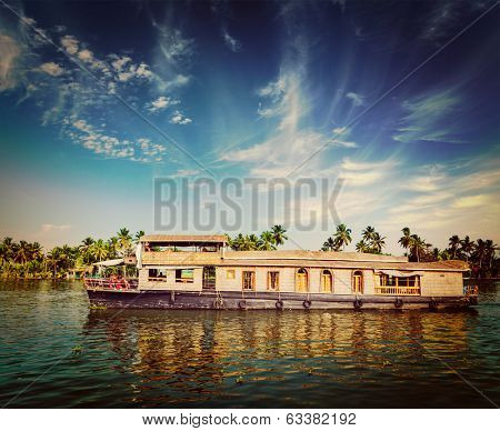 Vintage retro hipster style travel image of travel tourism Kerala background - houseboat on Kerala backwaters. Kerala, India