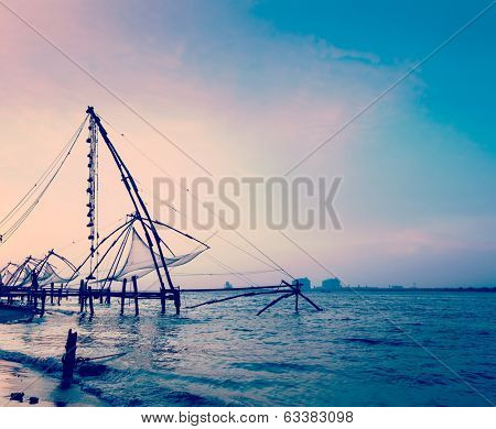 Vintage retro hipster style travel image of Kochi chinese fishnets on sunset. Fort Kochin, Kochi, Kerala, India