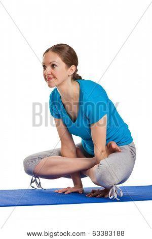 Yoga - young beautiful woman yoga instructor doing Cock Pose (Rooster Posture) (Kukkutasana) asana exercise isolated on white background
