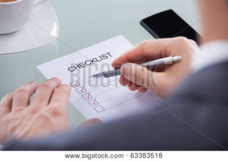 Businessperson With Pen Over Checklist