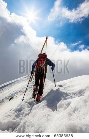 Ski mountaineer walking up along a steep snowy ridge with the skis in the backpack. In background a dramatic sky with a shiny bright sun. Concepts: adventure, achievement, courage, determination.