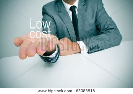 a businessman sitting in a desk showing the text low cost in his hand