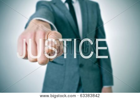 man wearing a suit pointing the finger to the word justice written in the foreground
