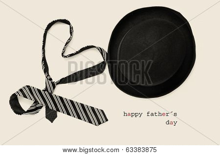 a tie forming a heart, a bowler hat and the sentence happy fathers day in a beige background, with a retro effect