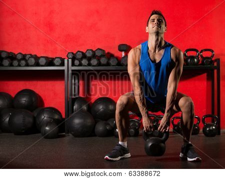 Kettlebell swing workout training man at gym with red walls