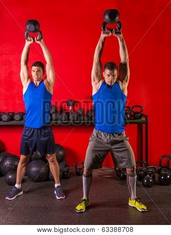 Kettlebell swing workout training group at gym with red wall