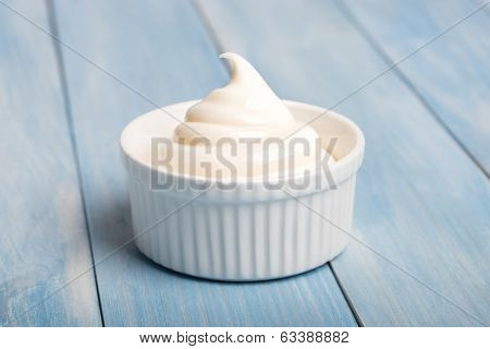 Portion of mayonnaise in a white ceramic dish,