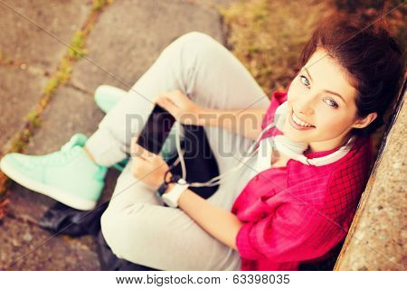 summer holidays and teenage concept - teenage girl with headphones listening to music outside