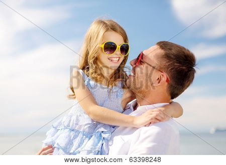 summer holidays, family, children and people concept - happy father and child girl having fun outdoors
