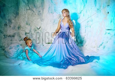 Little girl with mother in princess dress on a background of a winter fairy tale. Baby and mom snow queen. Sweet smiling child and mum snowy kingdom. Kid in in carnival costume