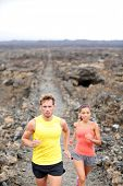 Trail running man and woman cross country runners jogging training outdoors for marathon run in beau