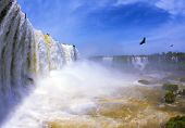 The  waterfall in the world - Iguazu. White whipped foam of water and a thin mist over the water. Th