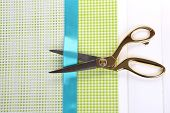Scissors on color fabric background