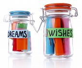 Dreams written on color  rolled paper in glass jar, isolated on white