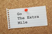 stock photo of mile  - The phrase Go The Extra Mile typed on a piece of lined note paper and pinned to a cork notice board - JPG