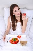 Young beautiful woman in bed with light breakfast