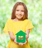 Girl holding a green house. Eco house. Ecology technology