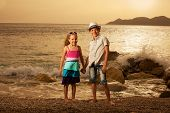 Children on the sea at sunset. Kids vacations.
