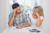 Worried young couple with financial documents and calculator sitting at home