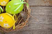 Easter eggs nest over wooden background