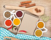 Various spices selection and notepad for copy space on wooden table