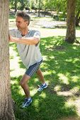 Full length of man stretching against tree in the park