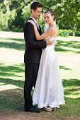 Full length of young newly wed couple embracing in garden