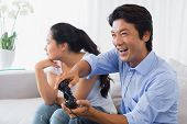 image of ignore  - Woman being ignored by boyfriend playing video games at home in the living room - JPG